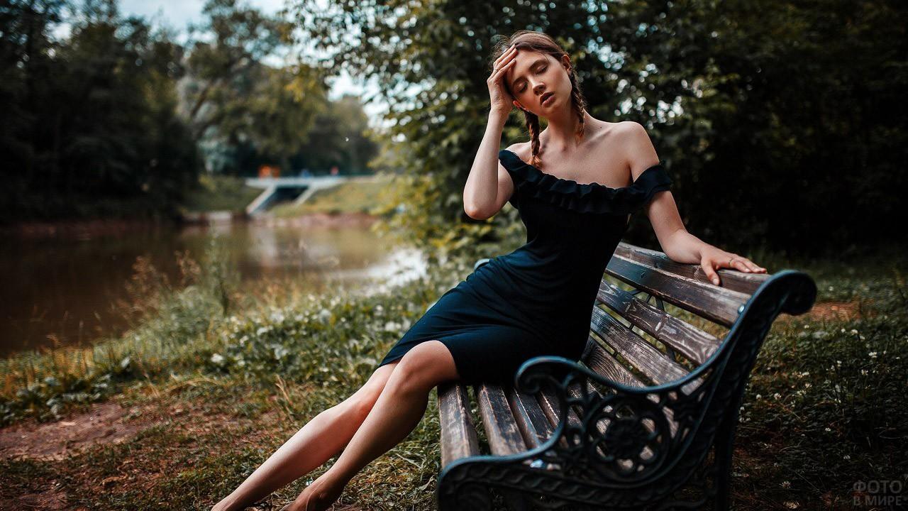 Девочка в платье с голыми плечами на скамейке в парке