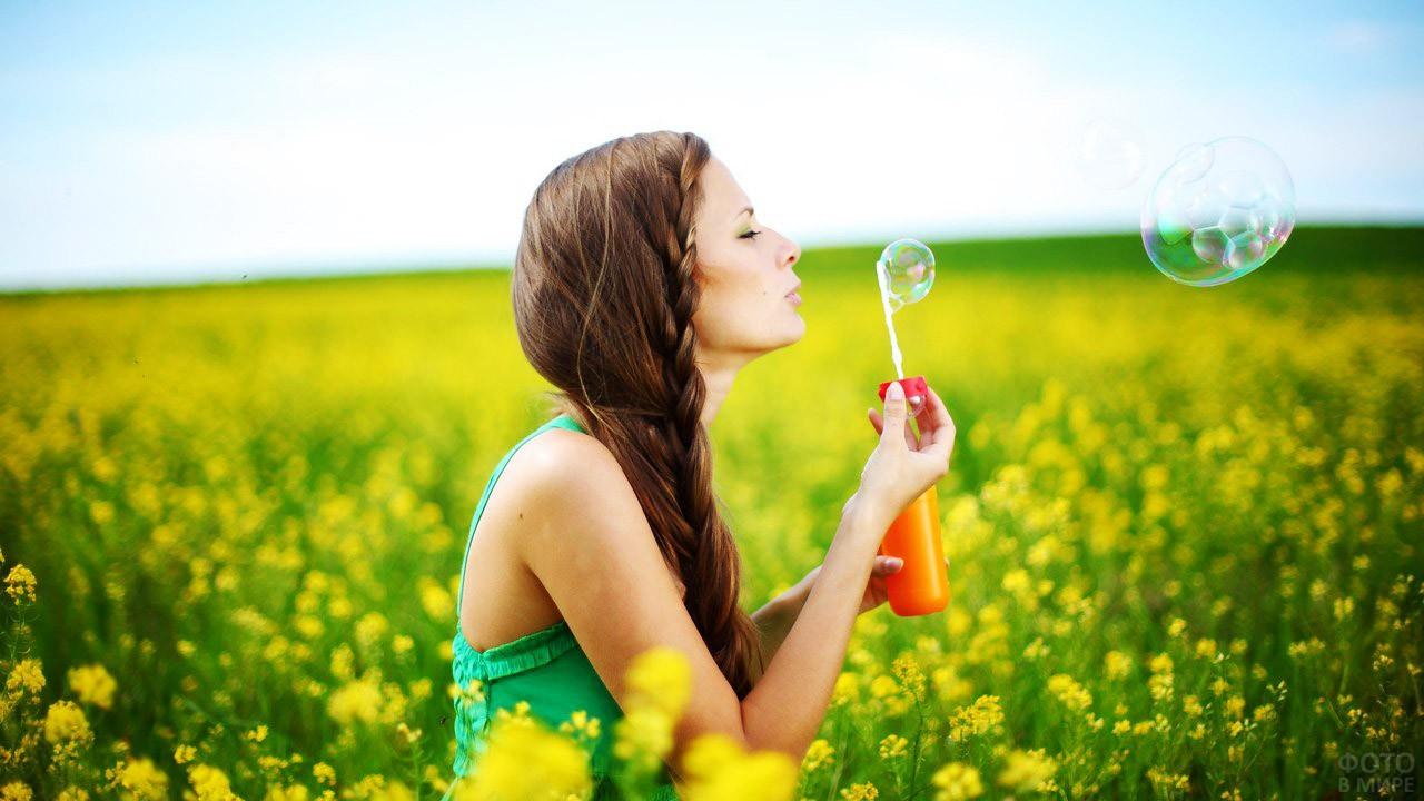 Девушка пускает мыльные пузыри в цветущем поле