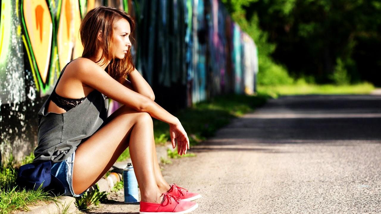 Девушка сидит у стены с граффити