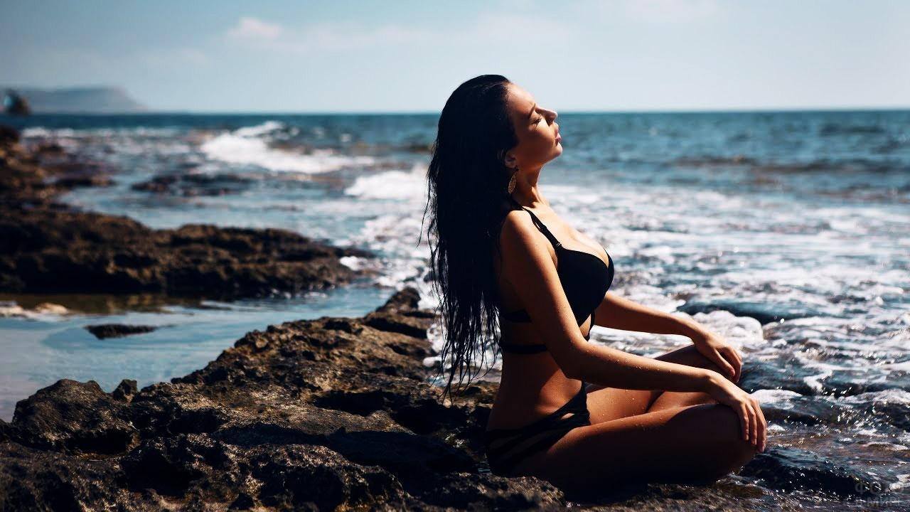 Гламурная брюнетка в чёрном бикини загорает у моря