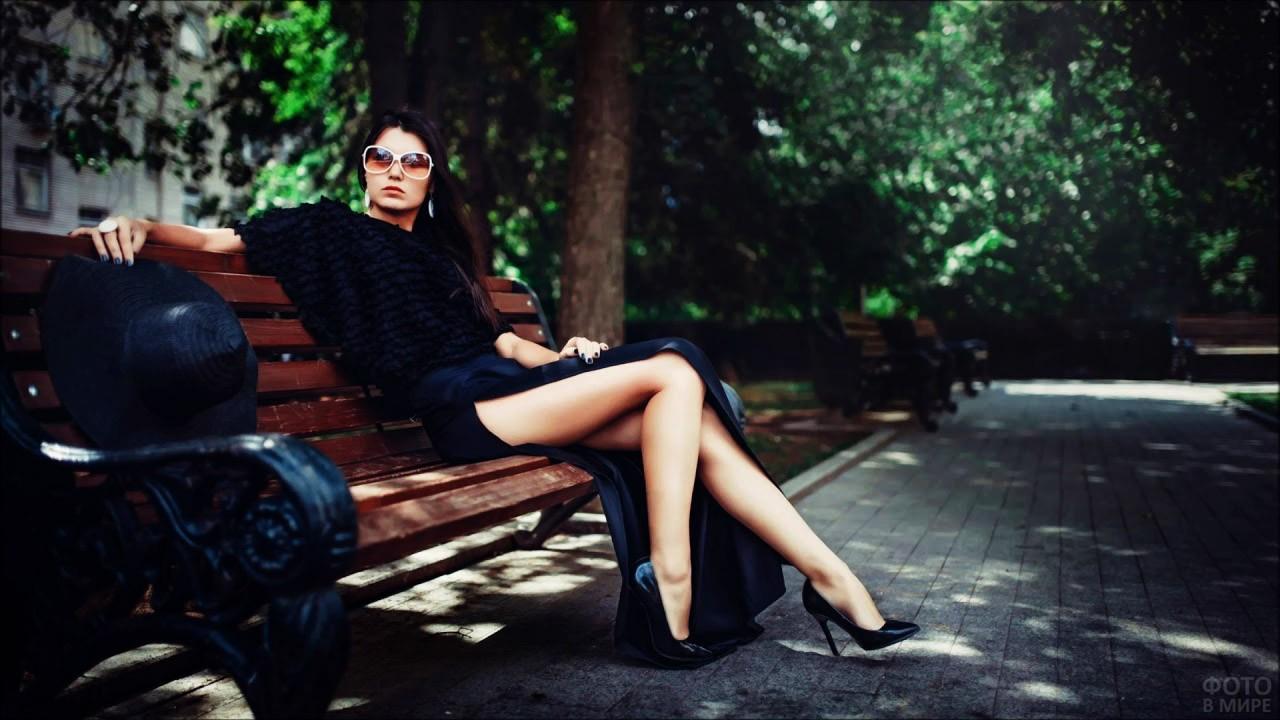 Гламурная брюнетка в чёрном на парковой скамье