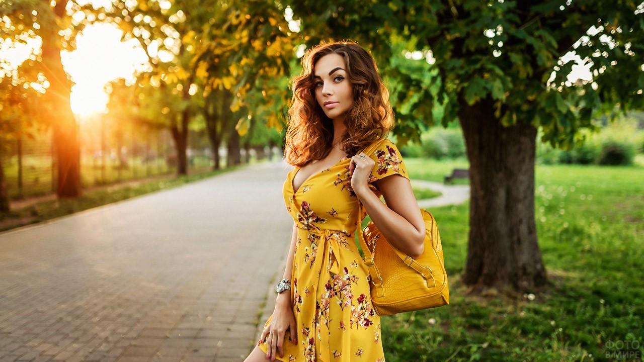 Гламурная красотка в жёлтом на закате дня в парке