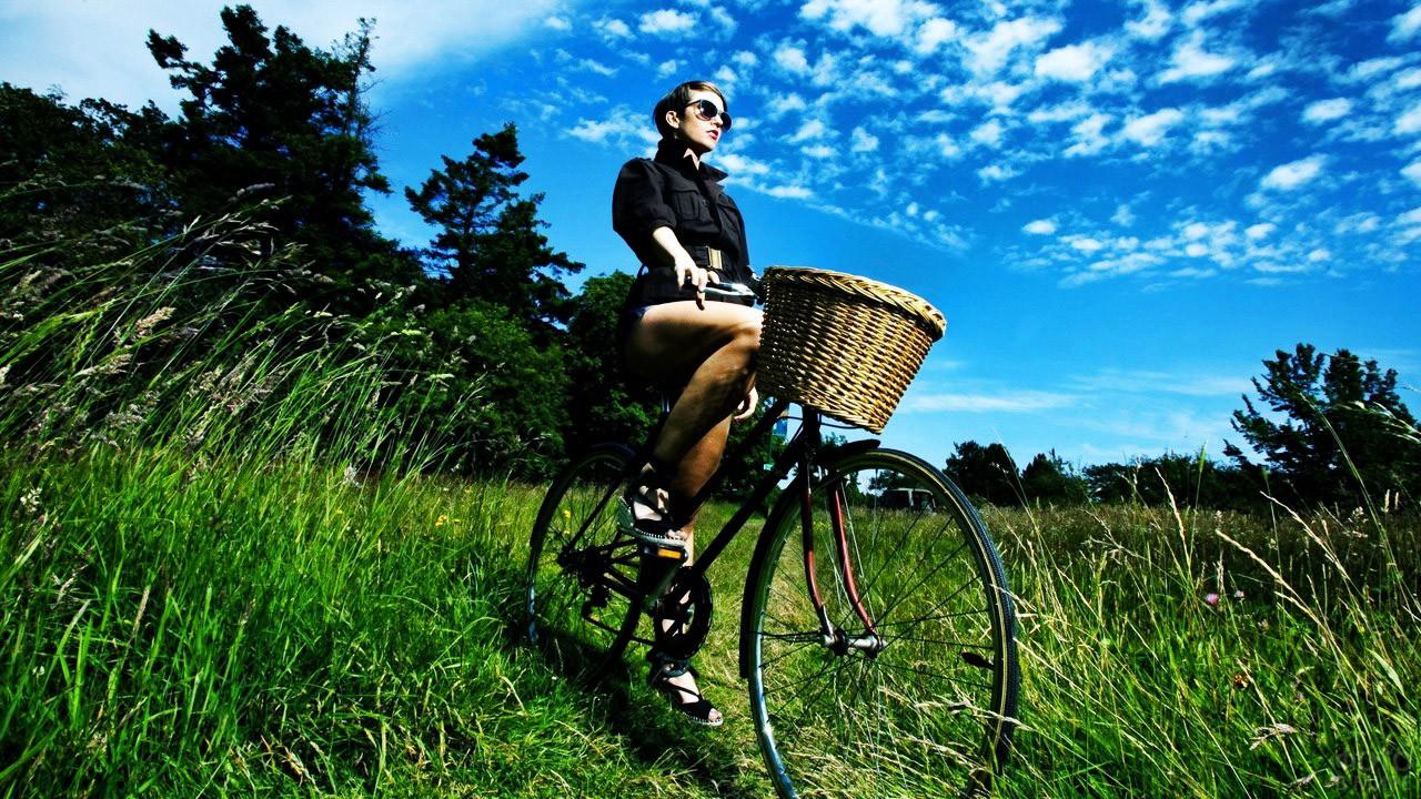 Гламурная модница на велосипеде посреди поля