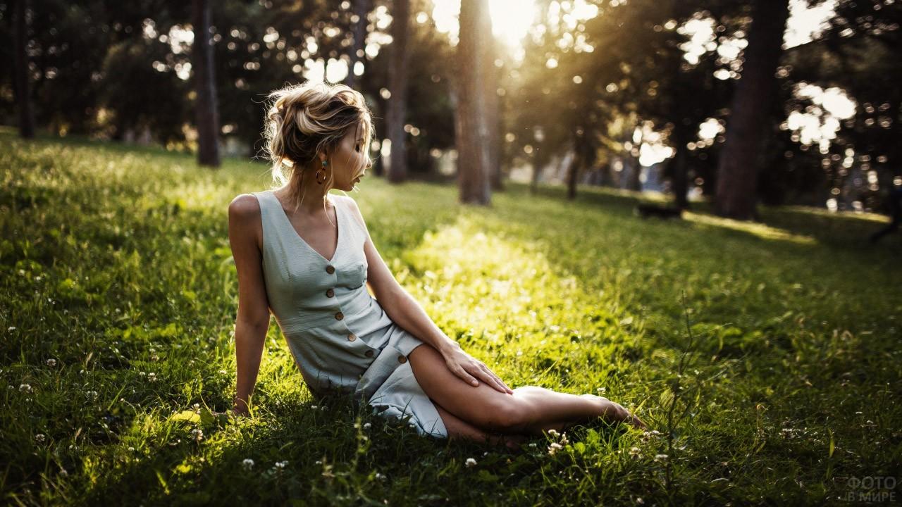 Хрупкая блондинка сидит на газоне