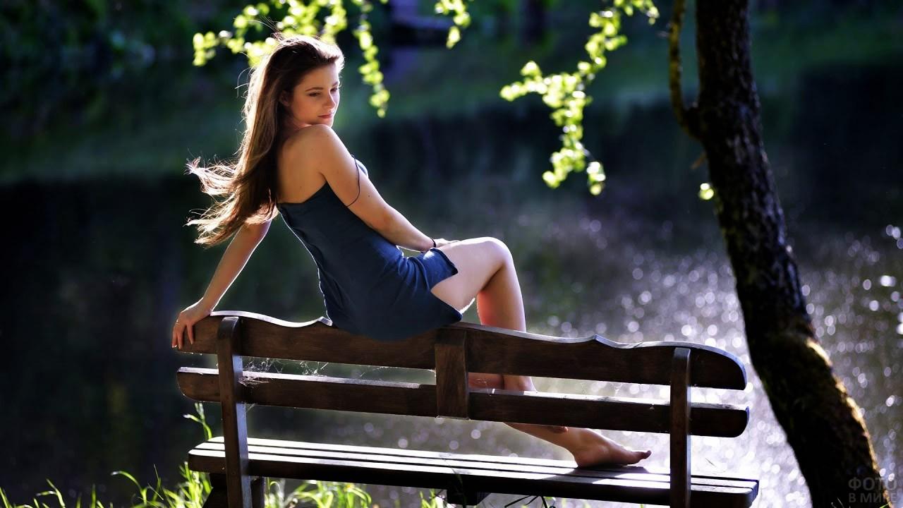 Красавица в лёгком сарафанчике на спинке садовой скамейки