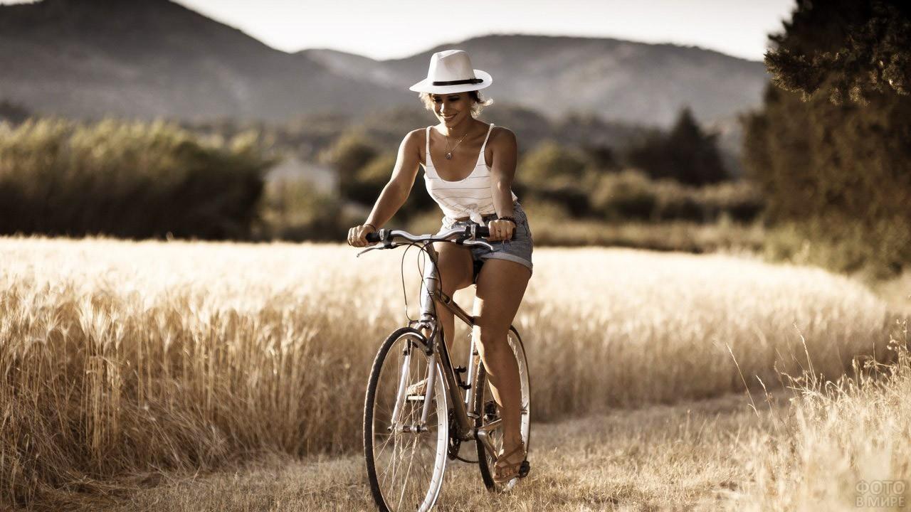 Симпатичная велосипедистка едет по полю