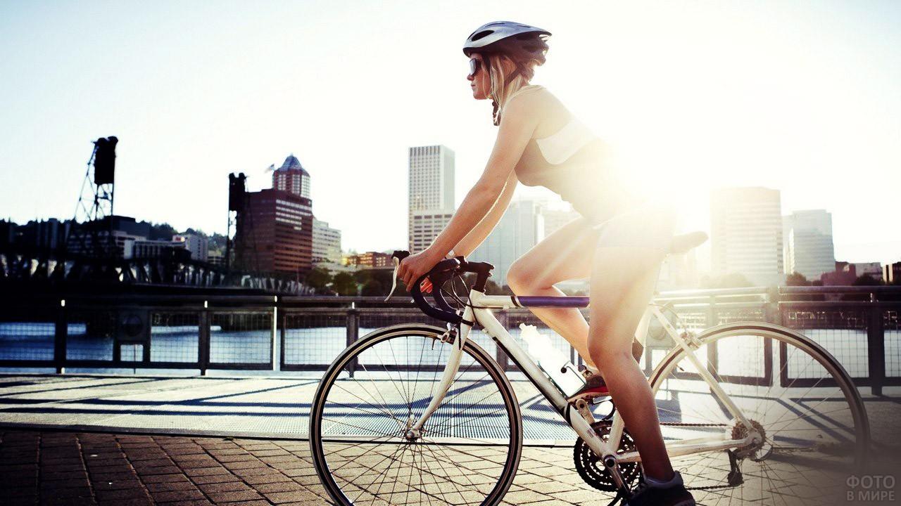 Спортивная блондинка едет по набережной в мегаполисе