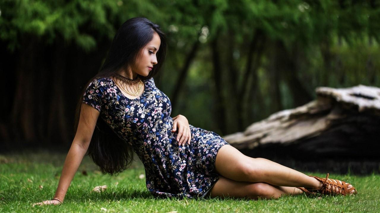 Стройная брюнетка в летнем платьице сидит на газоне
