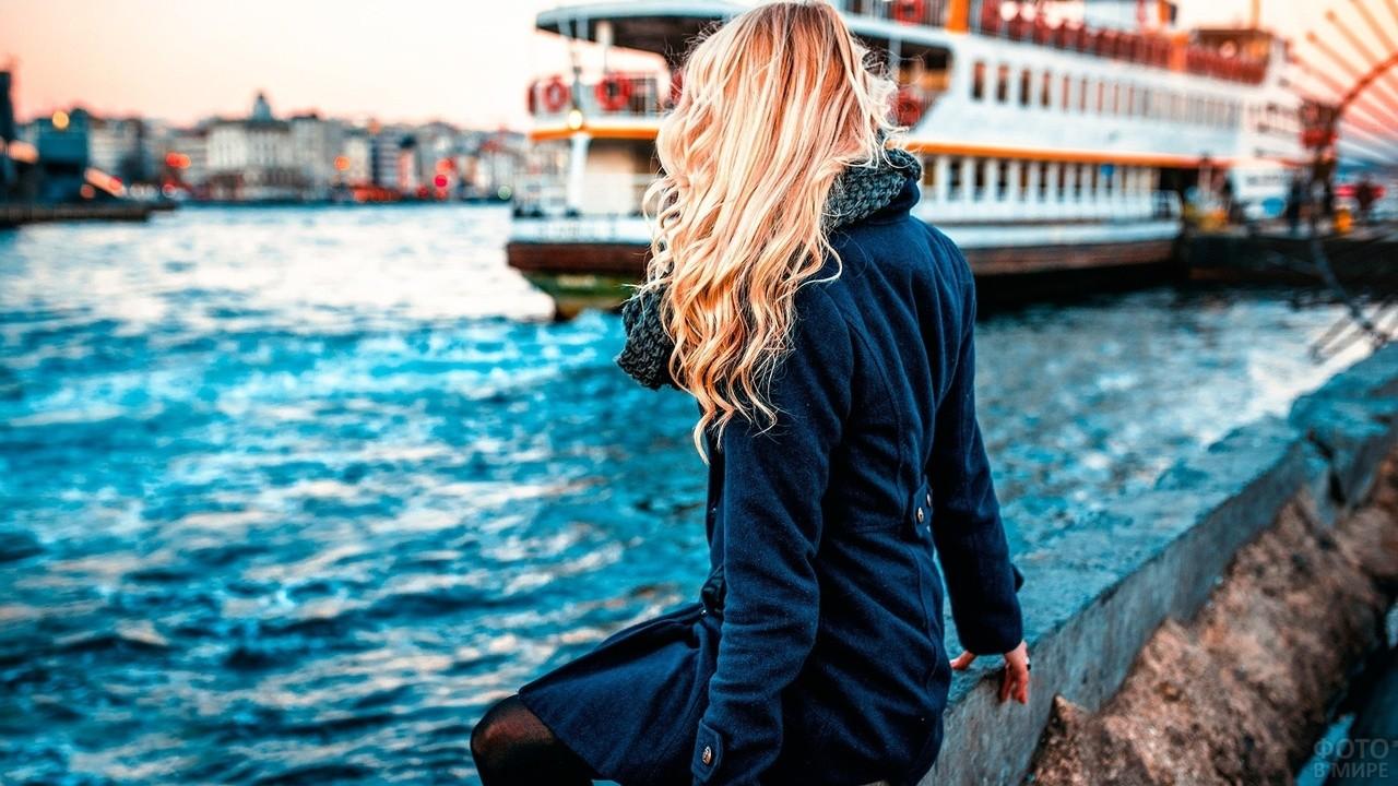 Блондинка в пальто сидит около воды