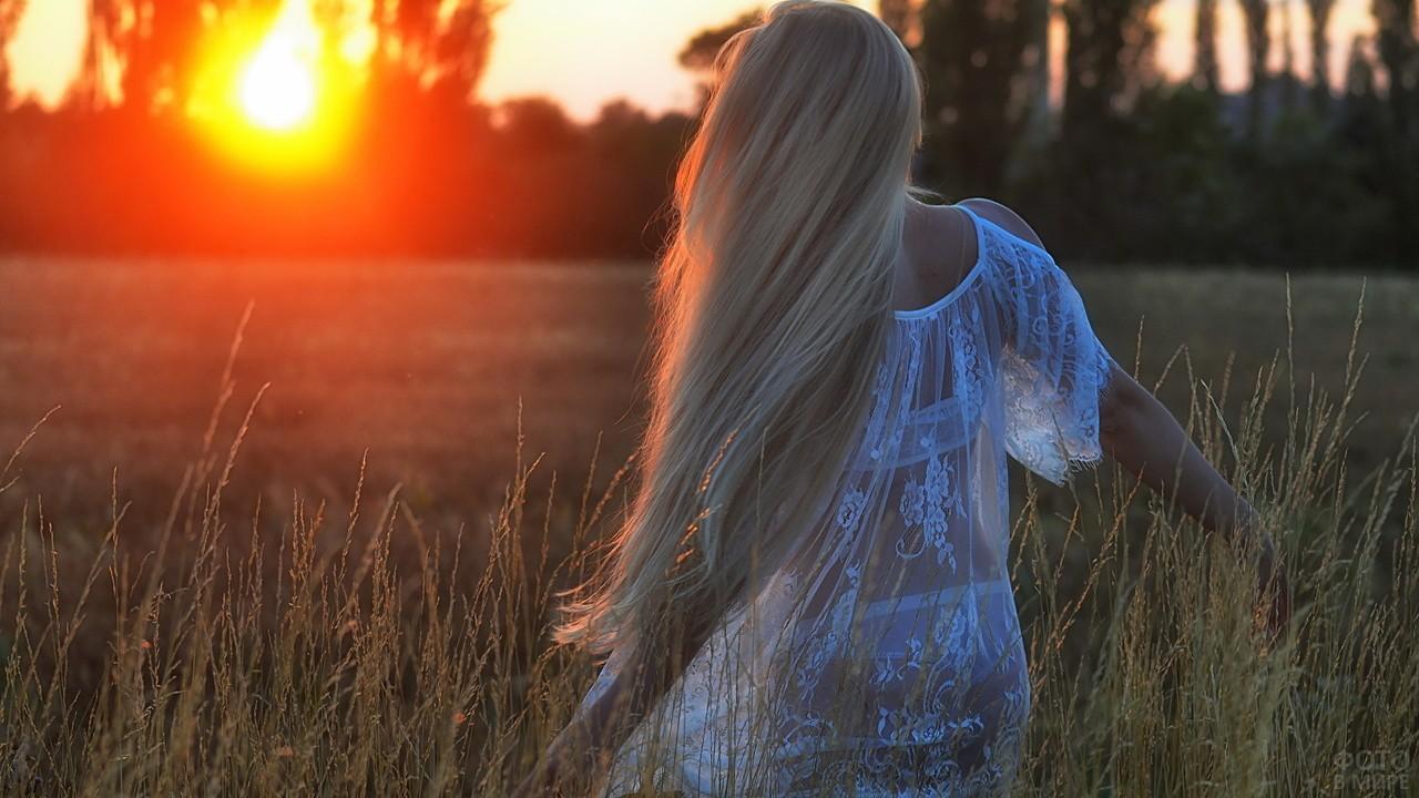 Блондинка в прозрачном платье смотрит на закат