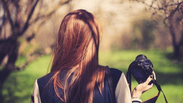Девушка с фотоаппаратом в руке
