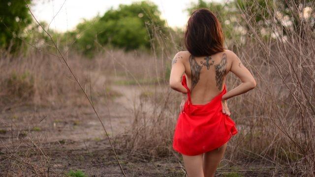 Девушка с татуировкой в кустах