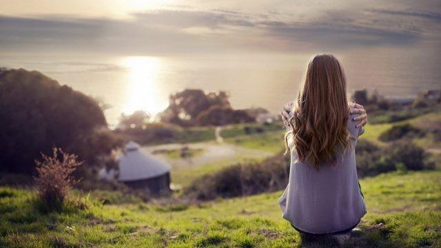 Девушка смотрит с возвышенности на дома и море