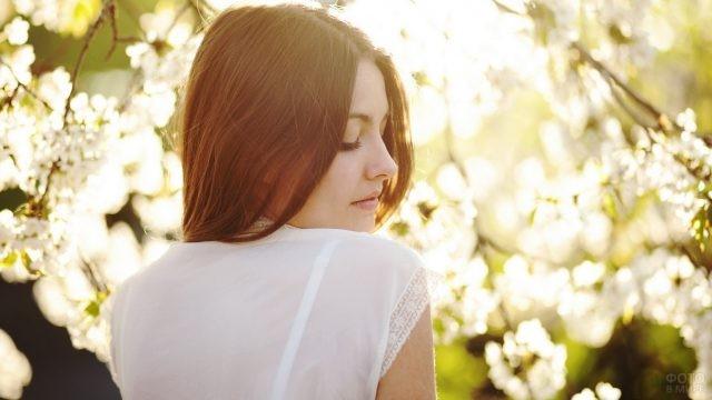 Девушка стоит около цветущего дерева