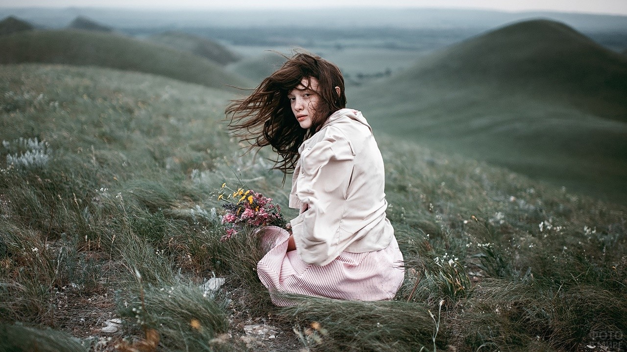 Девушка в ветренную погоду среди холмов