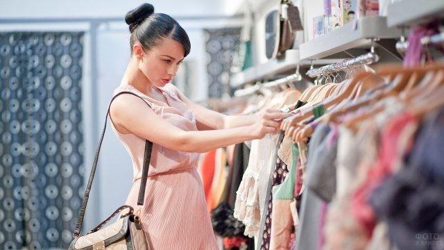 Брюнетка с сумкой через плечо выбирает платье