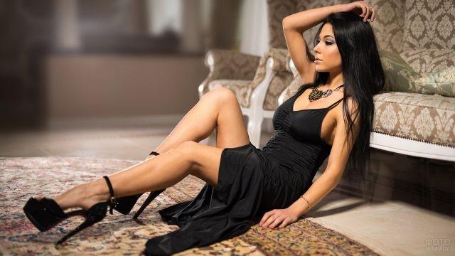 Брюнетка в черном платье на полу