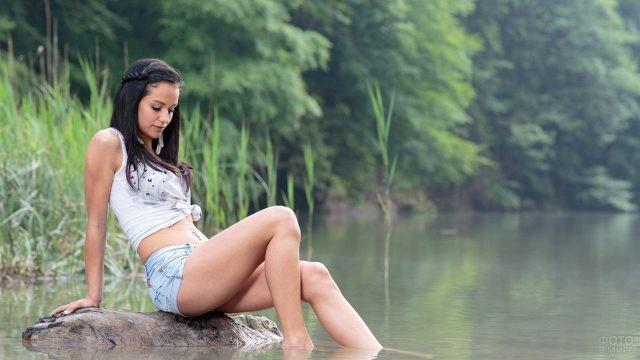 Черноволосая девушка сидит на камне посередине реки