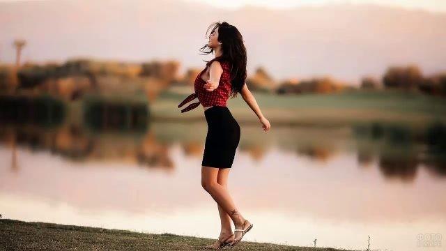 Черноволосая девушка танцует на берегу реки
