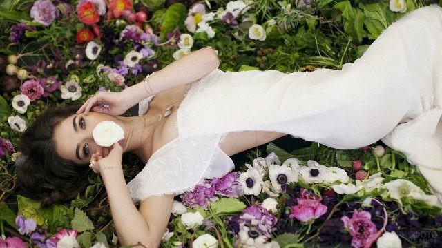 Черноволосая девушка в белом платье лежит на цветах