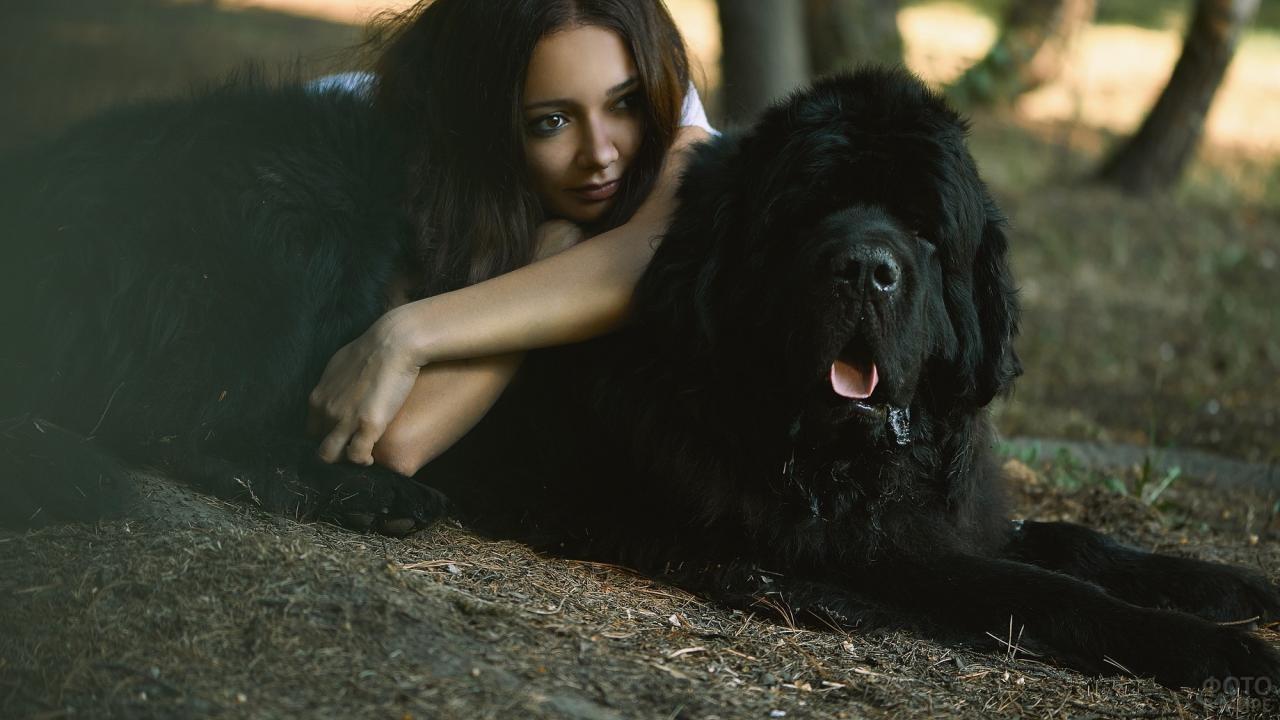 Девушка лежит на чёрной собаке