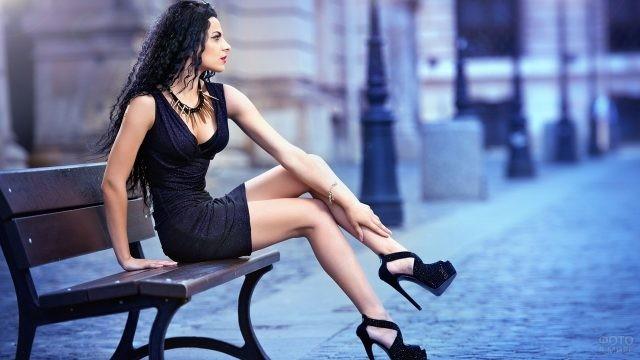 Девушка сидит на скамье в мини платье и высоких шпильках