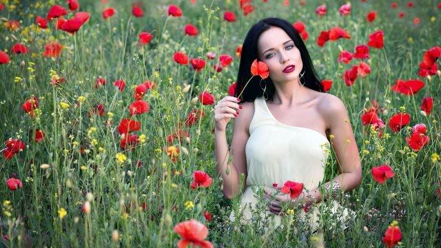 Девушка стоит среди красных маков