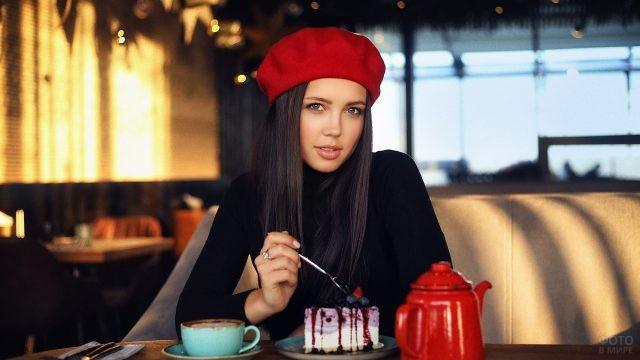 Девушка в красном берете ест пироженое