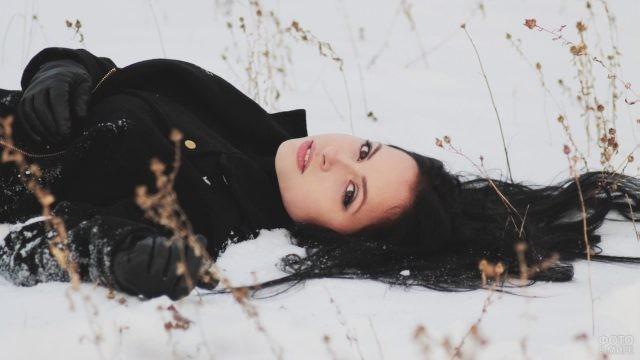 Девушка в пальто и перчатках лежит на снегу с распущенными волосами