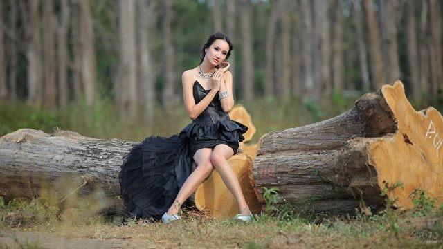 Девушка в вечернем платье сидит на бревне в лесу