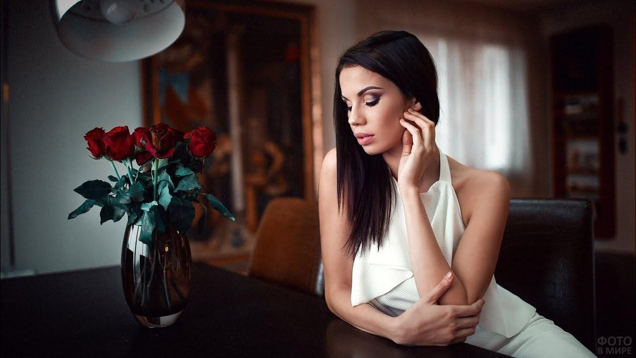Элегантная брюнетка сидит за столом перед вазой с розами