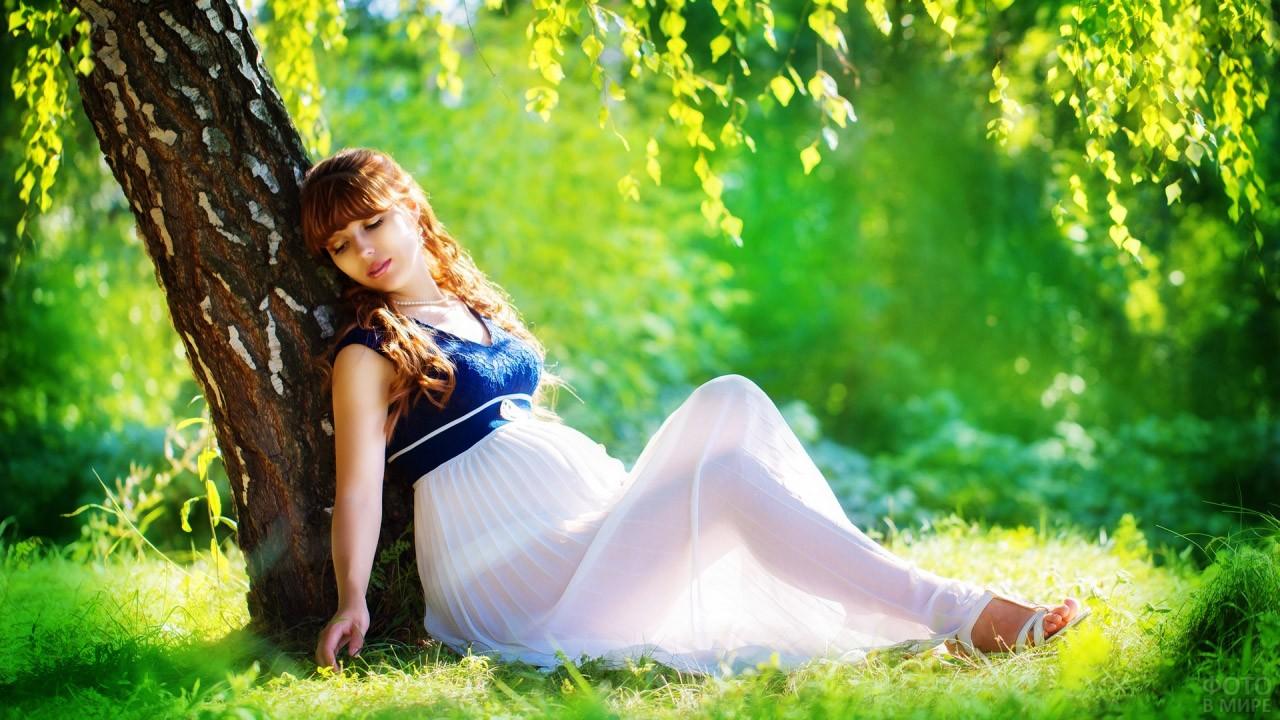 Беременная красавица сидит под берёзой