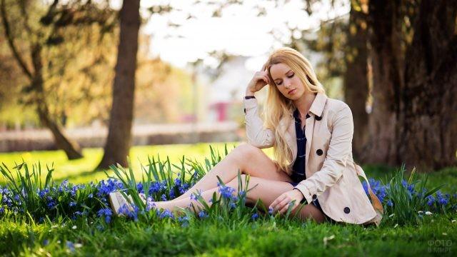 Блондинка сидит на лужайке среди первых цветов
