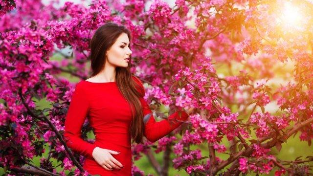 Брюнетка в красном платье среди цветущих деревьев
