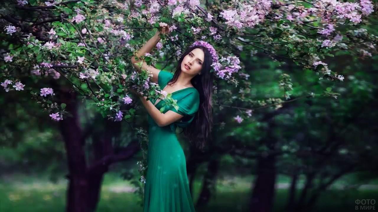 Брюнетка в зелёном платье под цветущим деревом