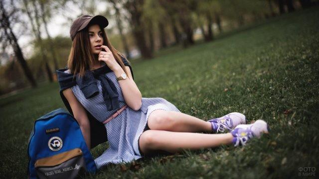 Девчушка в кепке и платьице сидит на газоне