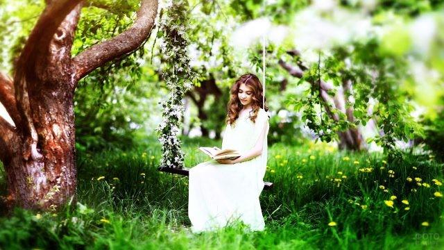 Девочка с ангельской внешностью на качелях под деревом