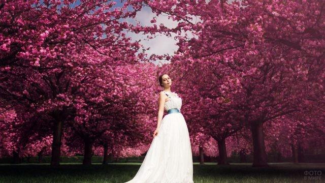 Девушка в белом платье в саду цветущей сакуры