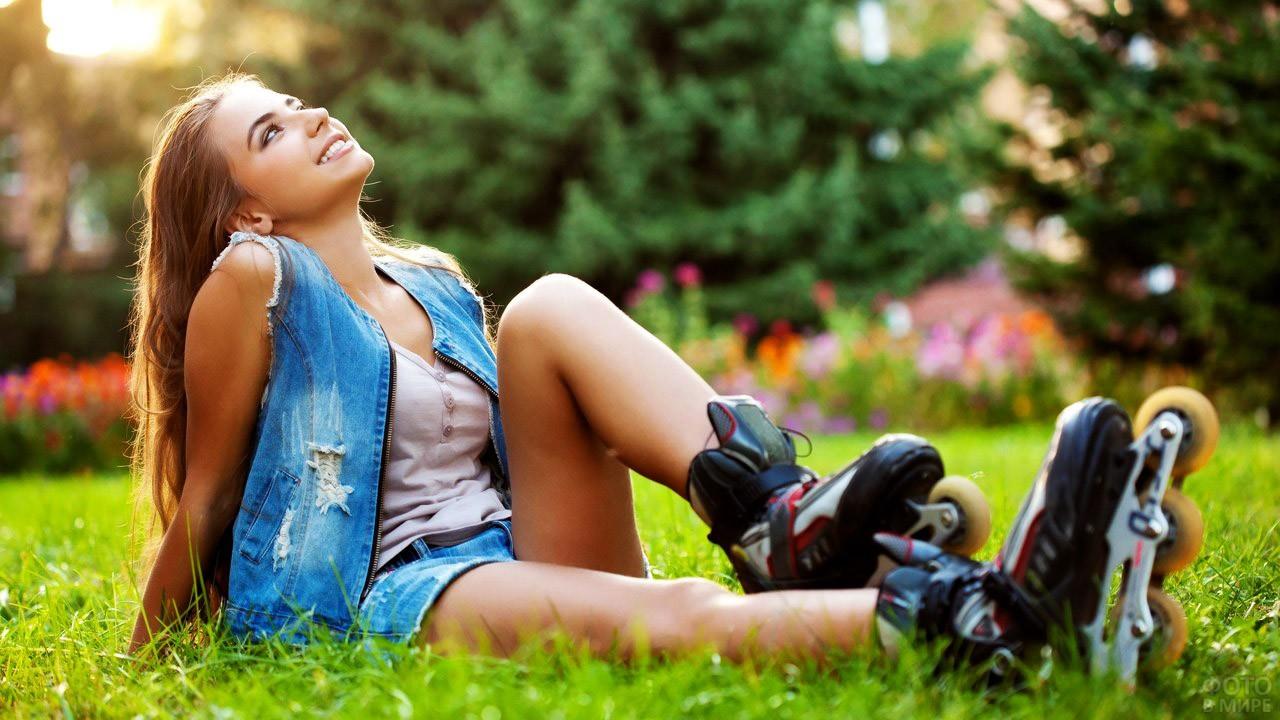 Девушка в роликах сидит на газоне