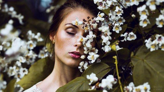 Хорошенькая девушка с веснушками среди цветов яблони