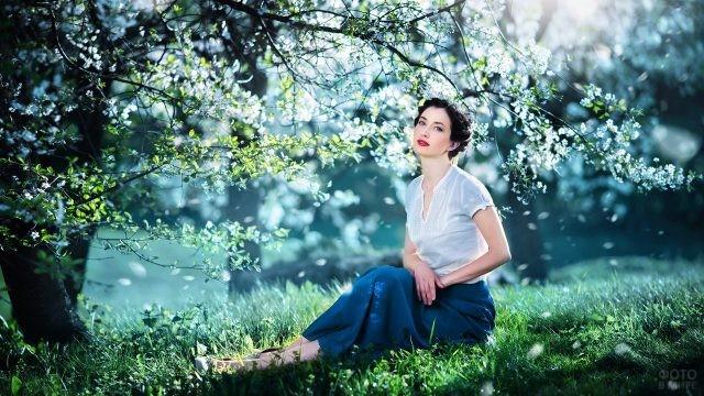 Элегантная красавица сидит под цветущим деревом