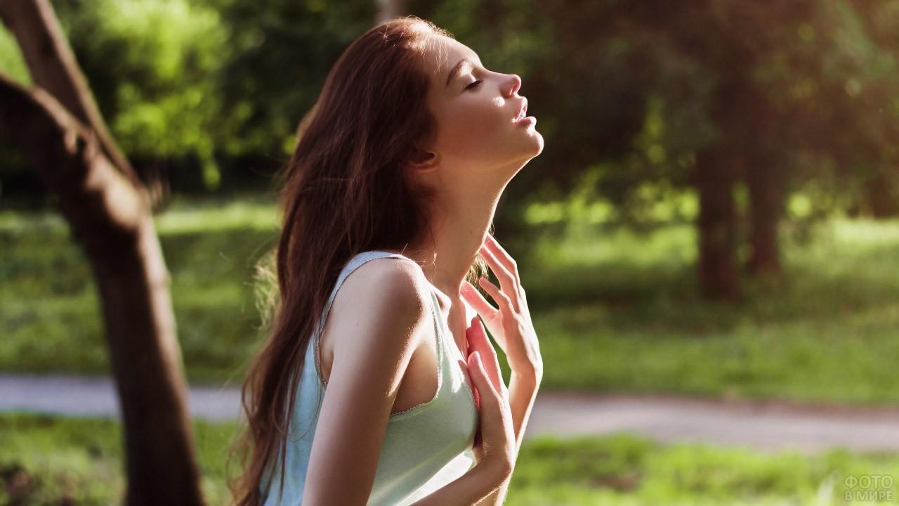 Юная длинноволосая девушка тянется лицом к солнцу