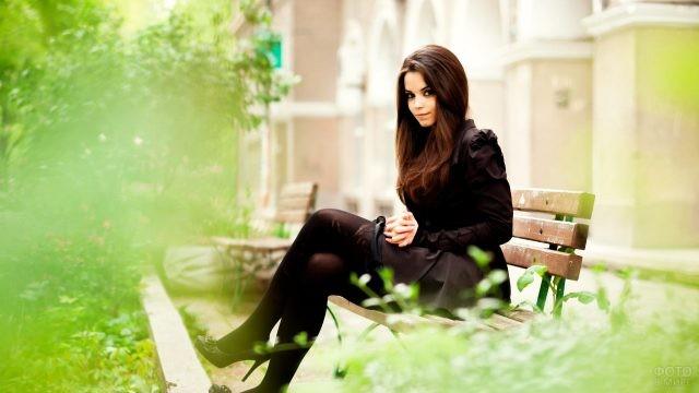 Юная красавица в чёрном на скамейке в весеннем парке