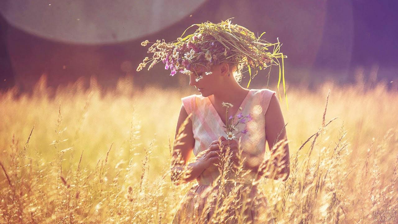 Красавица в пышном венке в цветущем поле