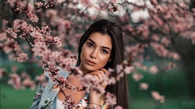 Миловидная брюнетка под цветущей яблоней