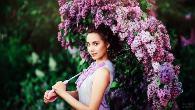 Русоволосая девушка с зонтиком из цветущей сирени