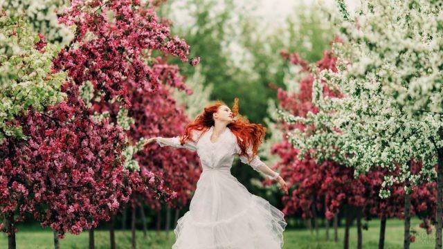 Рыжая девушка кружится в цветущем саду