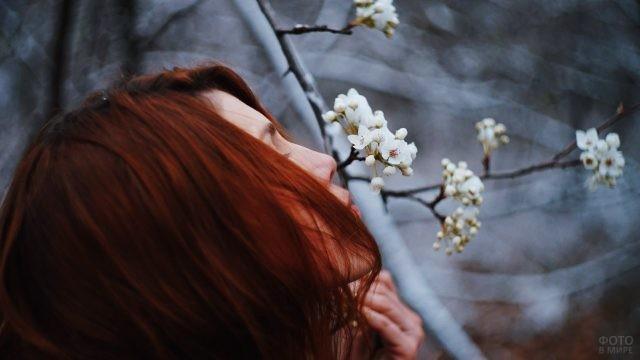 Рыжая девушка нюхает цветы яблони