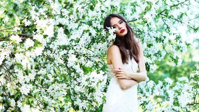 Шатенка в белом среди цветущих ветвей