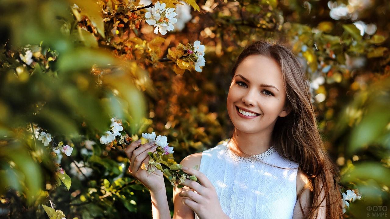 Улыбчивая девушка в цветущем саду